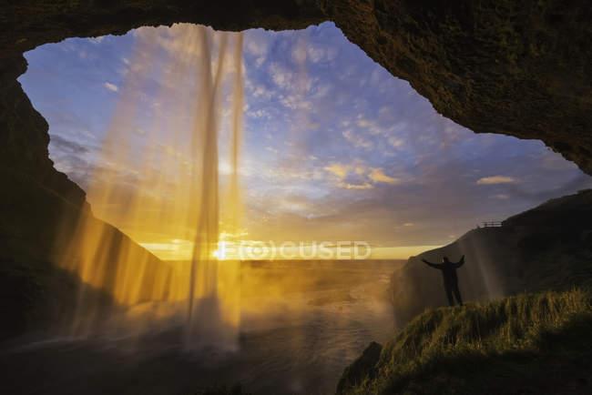 Человек, стоящий за водопадом — стоковое фото