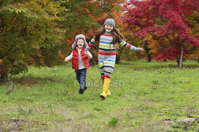 A young boy and girl wearing rubber boots and colourful clothing run across a field holding hands with trees in bright autumn colours in the background; Oregon, United States of America — Stock Photo