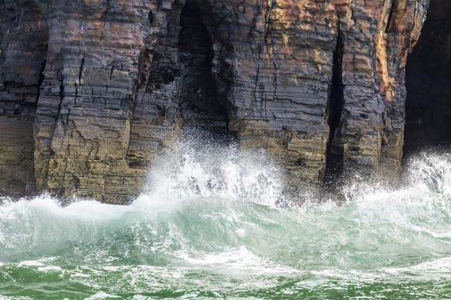Волны, врезаться в рок скалы — стоковое фото