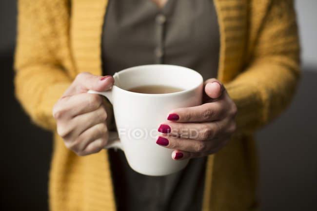 Женщина держит чашку чая в руках — стоковое фото