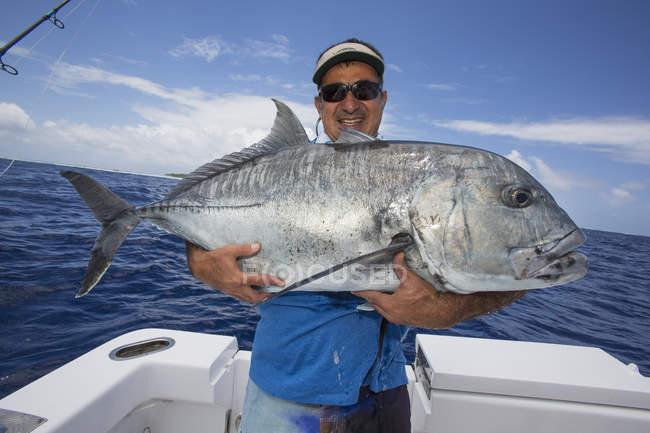 Fischer hält einen frischen Fisch Giant Trevally. Tahiti — Stockfoto