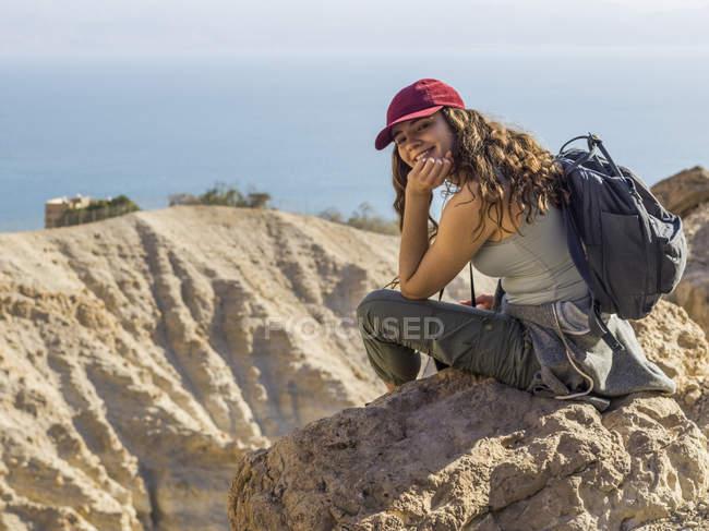 Junge Frau sitzt auf Felsen und Blick in die Kamera. Ein Gedi, Totes Meer, Israel — Stockfoto
