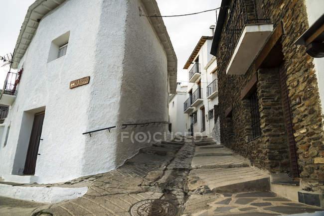 Calle inclinada entre casas - foto de stock