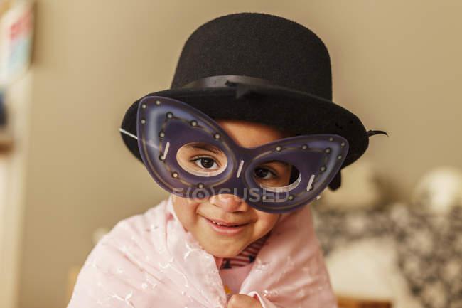 Junges Mädchen spielt verkleiden sich mit Maske und Hut — Stockfoto