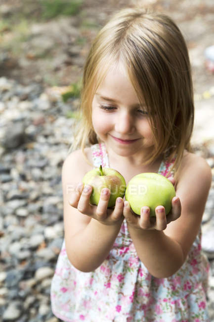 Young girl holding fresh apples — Stock Photo
