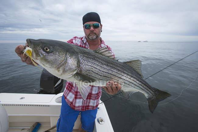 Fisherman holding striper fish in Boston harbour. Boston, Massachusetts, United States of America — Stock Photo