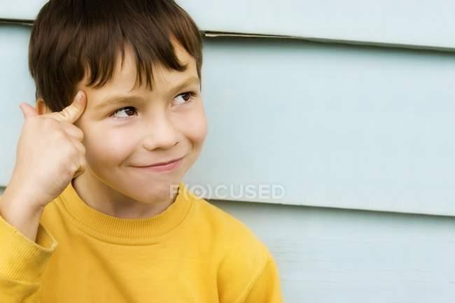 Молодой мальчик указывает головой к стене — стоковое фото