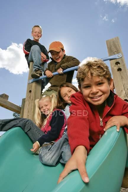 Пять детей, веселятся на детской площадке — стоковое фото