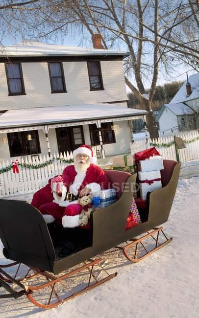 Père Noël sur son traîneau contre maison — Photo de stock