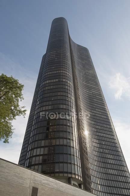 Rascacielos curvada contra el cielo nublado - foto de stock