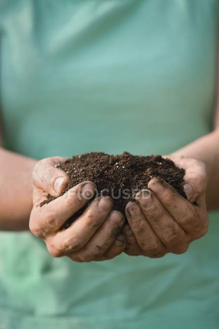 Cropped image of woman holding handful of soil — Stock Photo