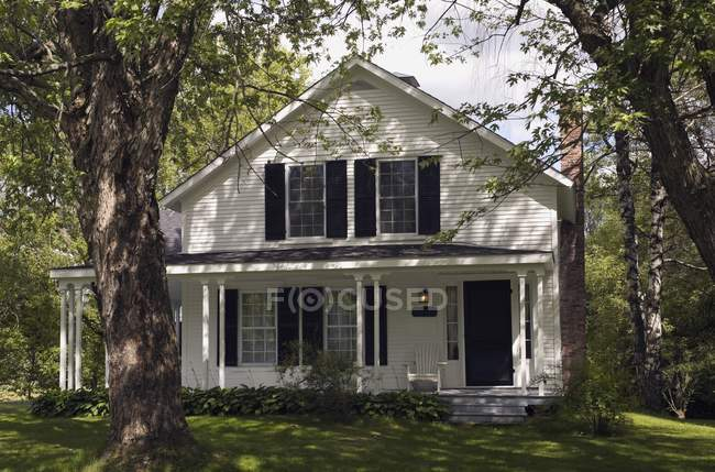 Facade of cottage house in shadows of trees — Stock Photo