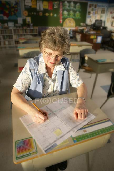 Happy mature female teacher sitting at school desk — Stock Photo