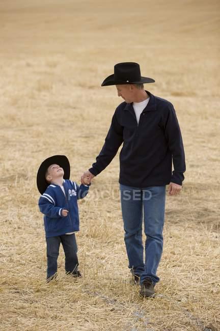 Людина і його син, носять Ковбойські капелюхи — стокове фото
