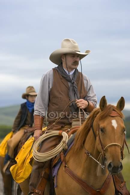 Vaqueros a caballo, sur de Alberta, Canadá - foto de stock