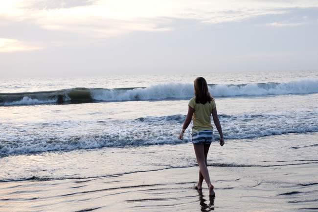 Підлітка дівчина, що йде на пляжі — стокове фото