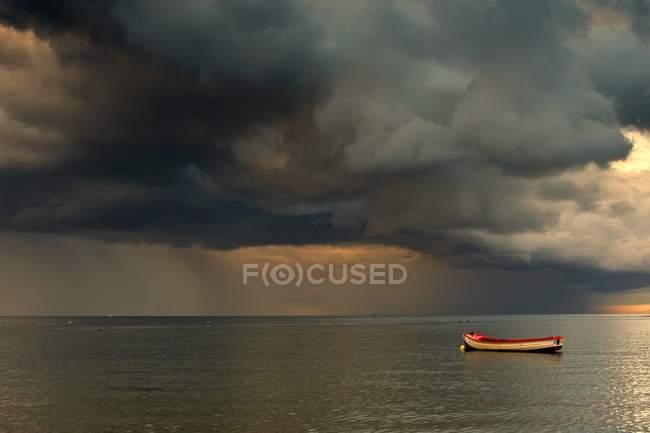 Темные облака и одинокая лодка — стоковое фото