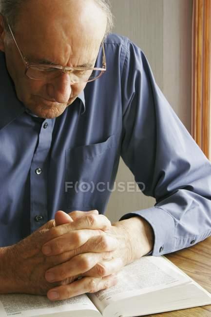 Älterer Mann mit der Bibel beten — Stockfoto