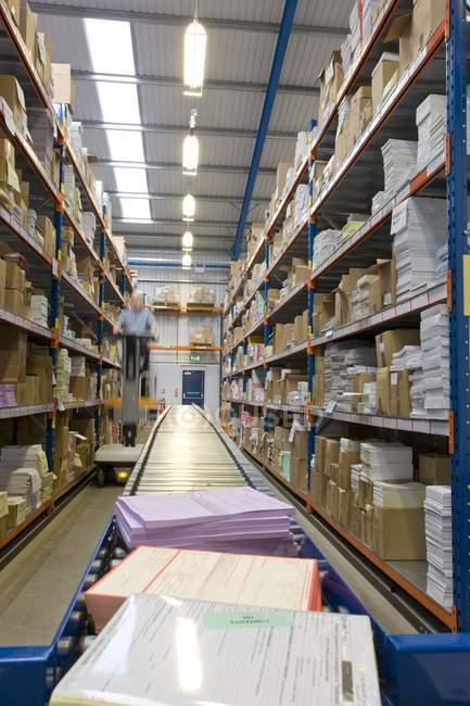 Bande transporteuse et garnie de tablettes en entrepôt — Photo de stock