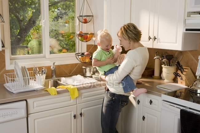 Madre caucásica e hija abrazando en la cocina y divertirse - foto de stock