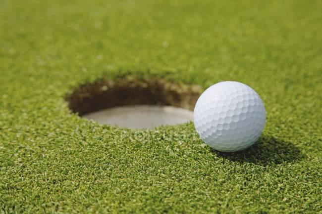 М'яч для гольфу поблизу отвір — стокове фото
