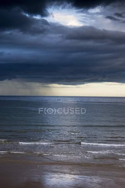 Буря проти піщаний пляж — стокове фото