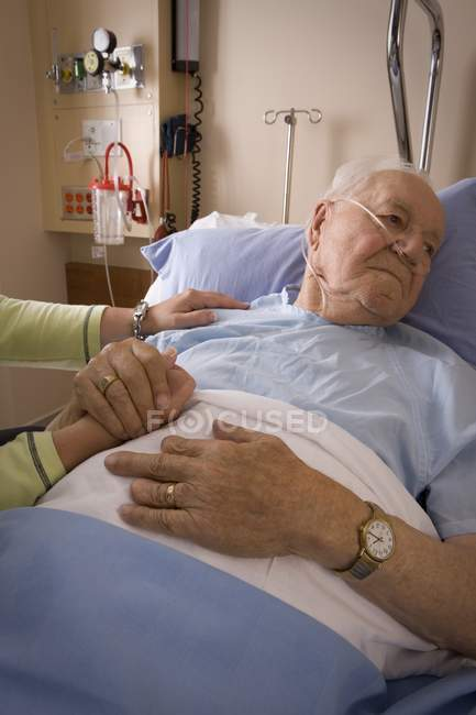 Senior Man In Hospital Bed Holding Hand Of Woman — Stock Photo