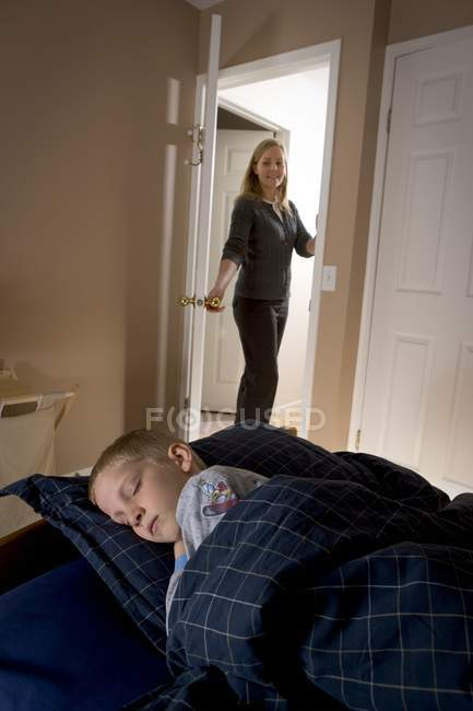 Mother coming to sons bedroom and watching at his sleep — Stock Photo