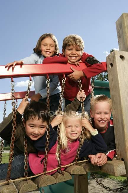 Cinco niños que se divierten en el patio - foto de stock