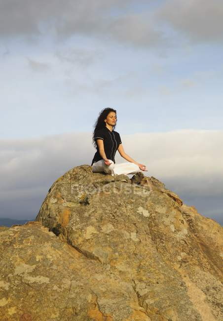 Woman meditating on top of boulder under sky — Stock Photo