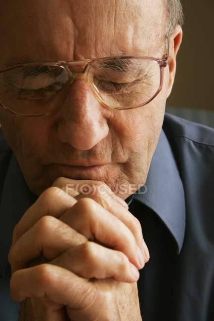 Літня людина молитися з закритими очима — стокове фото