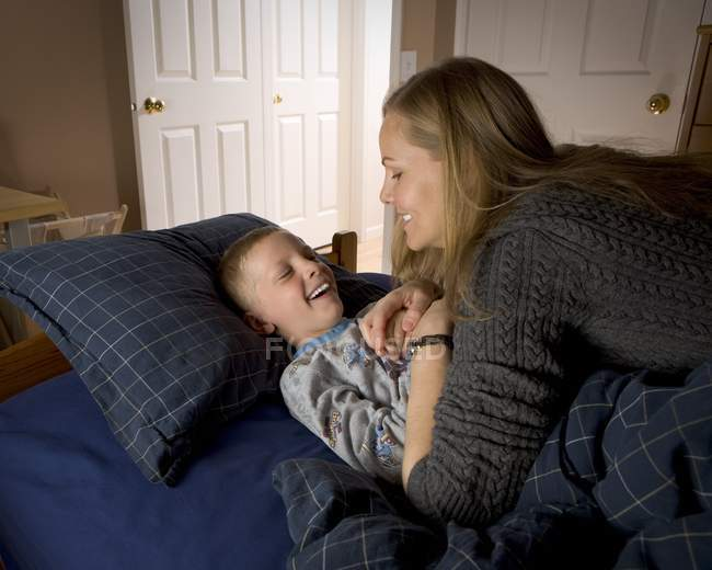 Cute laughing mother and son in bedroom — Stock Photo