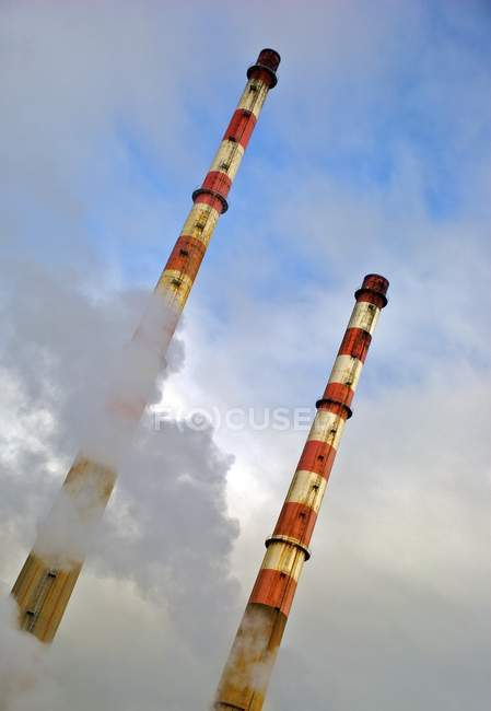 Smokestacks in front of blue sky — Stock Photo