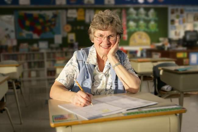 Щасливі зрілих вчителька сидячи за шкільною партою — стокове фото