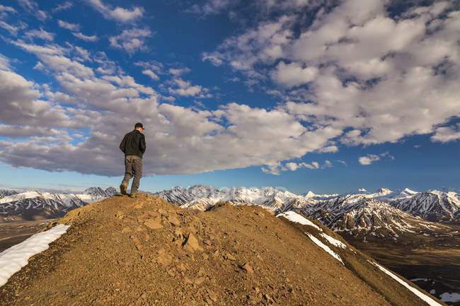 Male hiker standing on hill top against cloudy sky during aytime — Stock Photo