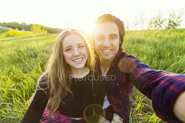 Junges romantisches Paar macht Sefie im Freien über grünem Gras und lächelt in die Kamera — Stockfoto