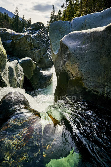 Kennedy River Carving It 's Way Between Large Rocks, Vancouver Island; British Columbia, Canadá - foto de stock