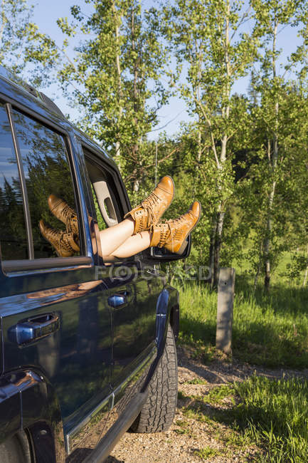 View of womans legs in boots on cars window edge against trees — Stock Photo