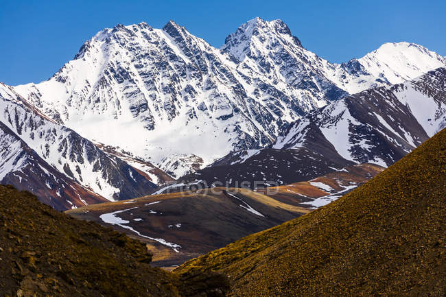 Snow covered mountain peaks with hills on foot during daytime — Stock Photo