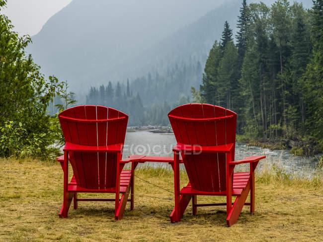 Duas cadeiras vermelhas de madeira na costa sobre a grama contra a água do lago com árvores e encostas na distância — Fotografia de Stock