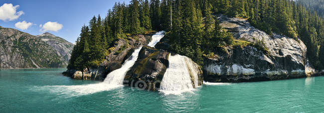 Waterfalls Over A Cliff Into The Water Along The Coastline In A Fjord; Alaska, United States Of America — Stock Photo