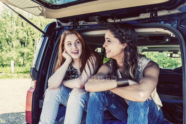 Two girls sitting at car while speaking with each other during daytime — Stock Photo
