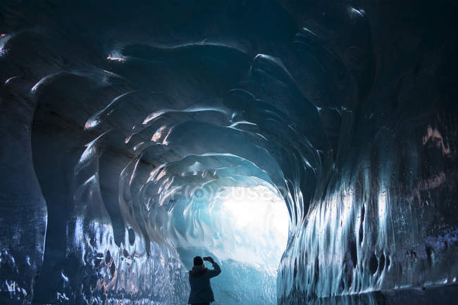 Rear view of woman standing in ice tunnel and making photo on smartphone — Stock Photo