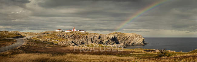 Rainbow over water and houses on cliff over sea water — Stock Photo