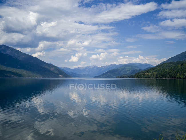 Eau calme du lac bleu et collines sous un ciel nuageux sur fond — Photo de stock