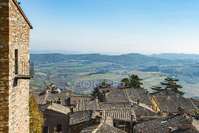 Panoramic View Of Colourful Tuscany Fields On A Blue Sky Background And Montepulciano City Tile Roofs; Tuscany, Italy — Stock Photo