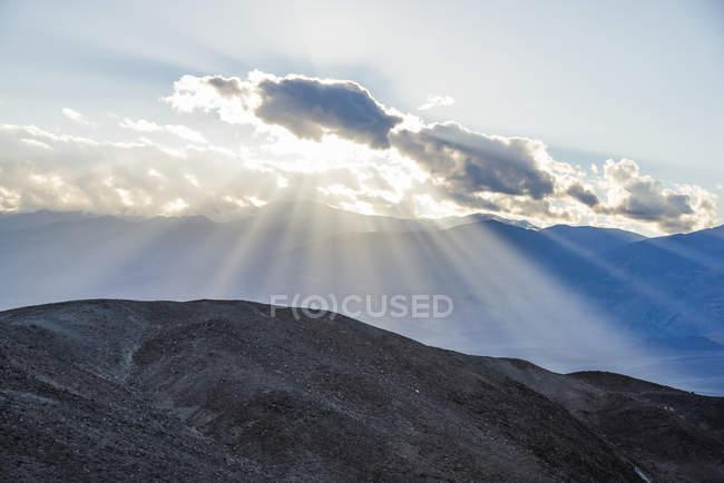 Потоки света из-за A облако в Долина смерти Национальный парк, рядом художников диска; Калифорния, Соединенные Штаты Америки — стоковое фото