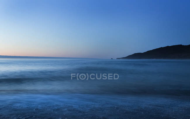 Tranquil sea water and hill on background at sunset — Stock Photo