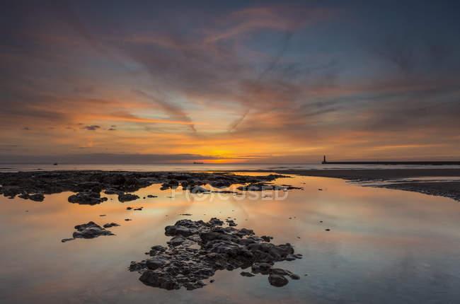 Vista del tramonto sulla riva con pietre contro l'acqua del mare calmo — Foto stock