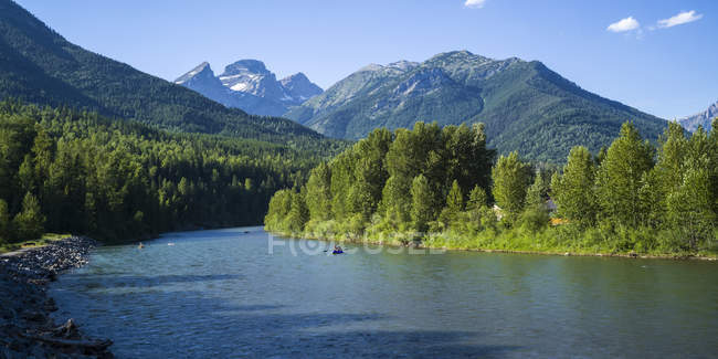 Lush trees on shore of mountain lake and peaks with hills on background — Stock Photo